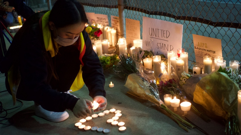 "A woman lights candles at a rally ""Stop Asian Hate"" candlelight vigil at Almansor Park in Alhambra, Calif., Saturday night, March 20, 2021. (AP Photo/Damian Dovarganes)"