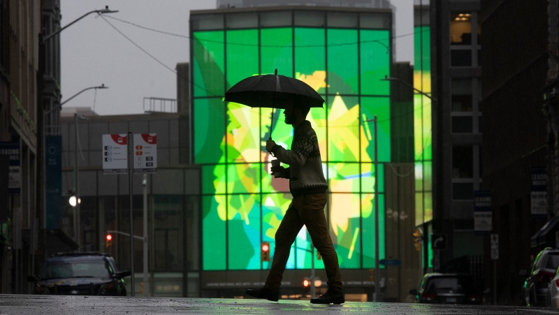 A man is silhouetted as he crosses the street near the National Arts Centre in downtown Ottawa, Friday March 26, 2021. (Adrian Wyld/THE CANADIAN PRESS)