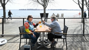 Diana Blaikie, left, and Bonnie Ryder have a cocktail on a outdoor patio at the Grain Urban Tavern while enjoying the warm weather along the boardwalk during the COVID-19 pandemic in Toronto on Thursday, March 25, 2021. THE CANADIAN PRESS/Nathan Denette