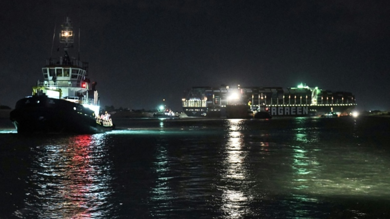 Tugboats work late into the night to dislodge the giant container ship that blocked traffic through the vital Suez Canal. (AFP)
