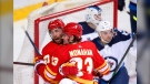 Calgary Flames' Josh Leivo (27) celebrates his goal with teammate Sean Monahan in front of Winnipeg Jets goalie Laurent Brossoit and Neal Pionk during first period NHL hockey action in Calgary, Alta., Saturday, March 27, 2021. THE CANADIAN PRESS/Todd Korol