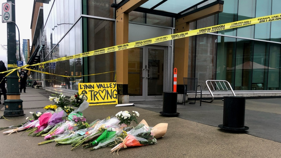 Crime scene tape cordons off the area in Lynn Valley where six people were injured and one killed after a stabbing incident on Saturday, and flowers placed near the scene, in the District of North Vancouver, could be seen on Sunday, March 28, 2021.