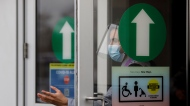 A security guard gestures as people arrive at the City of Toronto operated mass COVID-19 vaccination site in East York Town Centre, servicing the Thorncliffe Park community, an area disproportionally impacted by COVID-19, Wednesday, March 24, 2021. THE CANADIAN PRESS/Cole Burston