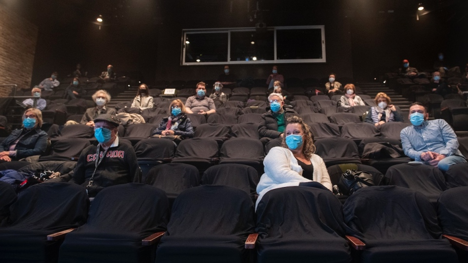 People wear face masks as they wait for the start of a performance of MOB at the Centaur Theatre in Montreal, Sunday, March 28, 2021, as the COVID-19 pandemic continues in Canada and around the world. Certain health and safety measures have been eased in the province of Quebec allowing theatres, churches and gyms to have up to 250 people on their premises. THE CANADIAN PRESS/Graham Hughes