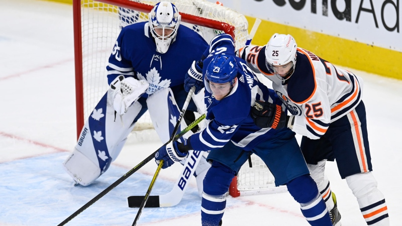 Toronto Maple Leafs defenceman Travis Dermott (23) battles Edmonton Oilers defenceman Darnell Nurse (25) for control of the puck as Leafs goaltender Michael Hutchinson (30) looks on during first period NHL hockey action in Toronto on Monday March 29, 2021. THE CANADIAN PRESS/Frank Gunn