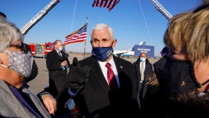 Former U.S. Vice-President Mike Pence greets supporters after arriving back in his hometown of Columbus, Ind., Wednesday, Jan. 20, 2021. (AP Photo/Michael Conroy)
