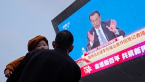 A man carries a child near a giant screen displaying Chinese Premier Li Keqiang at a press conference held after the closing of the National People's Congress in Beijing on Thursday, March 11, 2021. (AP Photo/Ng Han Guan)