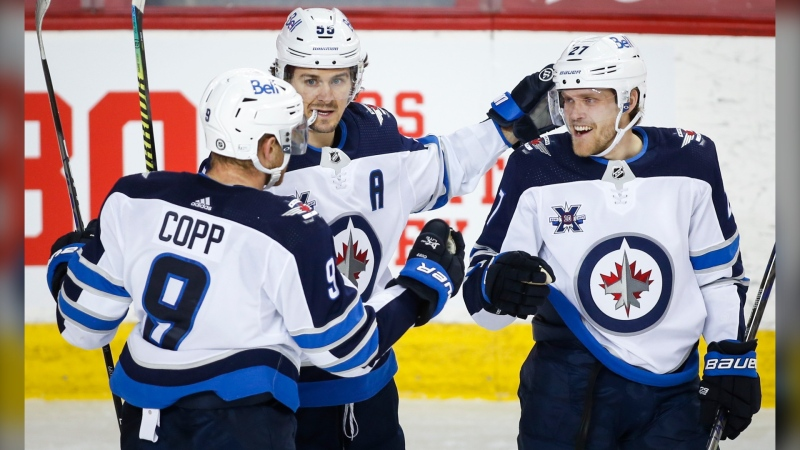 Winnipeg Jets' Andrew Copp, left, celebrates his goal with teammates Mark Scheifele, centre, and Nikolaj Ehlers during second period NHL hockey action against the Calgary Flames in Calgary, Monday, March 29, 2021. THE CANADIAN PRESS/Jeff McIntosh