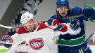 Vancouver Canucks centre Adam Gaudette (96) and Montreal Canadiens defenceman Brett Kulak (77) fight for control of the puck during second period NHL action in Vancouver, Monday, March 8, 2021. (Jonathan Hayward / THE CANADIAN PRESS)