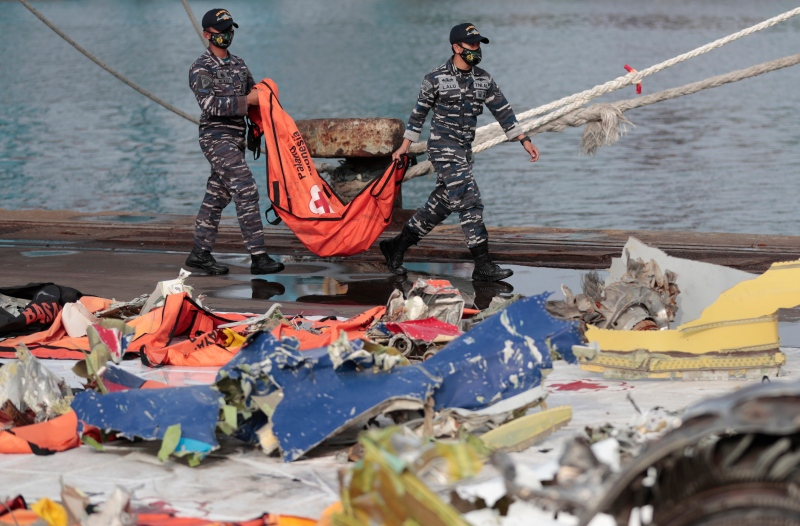 Navy sailors carry a body bag containing the recovered remains of victims of the Sriwijaya Air flight SJ-182 that crashed on Jan. 9, at Tanjung Priok Port in Jakarta, Indonesia, Thursday, Jan. 21, 2021. (AP Photo/Dita Alangkara)