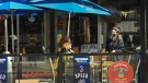 A waitress works the outdoor patio at a restaurant in Little Italy during the COVID-19 pandemic in Toronto on Tuesday, March 30, 2021. THE CANADIAN PRESS/Nathan Denette