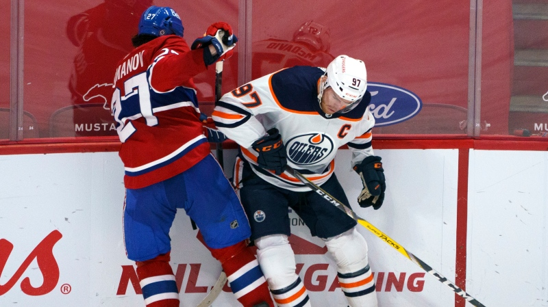 Montreal Canadiens' Alexander Romanov and Edmonton Oilers' Connor McDavid (97) battle for the puck during second period NHL hockey action in Montreal on Tuesday, March 30, 2021. THE CANADIAN PRESS/Paul Chiasson