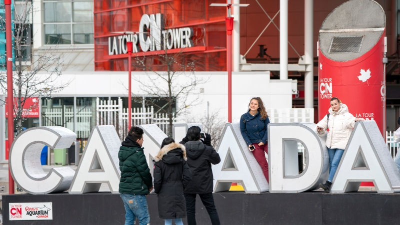 Tourists pose for photos at the base of the CN Tower in Toronto on Saturday, March 14, 2020 . THE CANADIAN PRESS/Frank Gunn