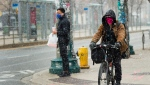 A man cycles in a snow with a mask on in downtown Toronto on Thursday, April 16, 2020. Health officials and the government have asked that people stay inside to help curb the spread of COVID-19. THE CANADIAN PRESS/Nathan Denette