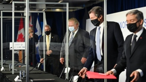 Ontario Premier Doug Ford, centre, along with two levels of government are divided with plexiglass barriers as they announced 925 million in funding to expand Canada's vaccine manufacturing capacity with Sanofi Pasteur Ltd., during the COVID-19 pandemic in Toronto on Wednesday, March 31, 2021. THE CANADIAN PRESS/Nathan Denette