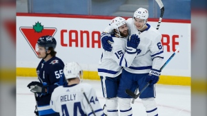 Toronto Maple Leafs' Alexander Kerfoot (15) and Ilya Mikheyev (65) celebrate Kerfoot's goal against the Winnipeg Jets during second period NHL action in Winnipeg on Wednesday, March 31, 2021. THE CANADIAN PRESS/John Woods