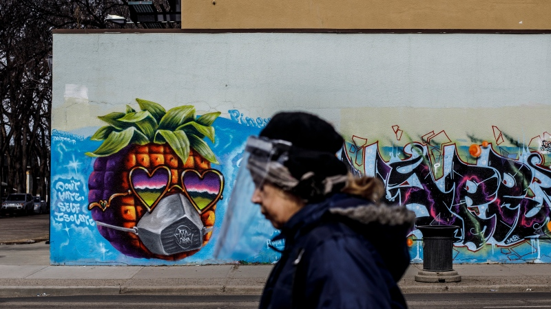 A person wearing a protective face shield walks past a mural during the COVID-19 Pandemic, in Edmonton Alta, on Wednesday April 15, 2020 (THE CANADIAN PRESS/Jason Franson).