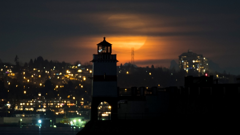 The pink supermoon rises behind the lighthouse on Brockton Point in Stanley Park in Vancouver, B.C., Wednesday, April 8, 2020. THE CANADIAN PRESS/Jonathan Hayward
