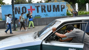 "A man pushes his car that ran out of gas as people wearing protective face masks as a precaution against the spread of the new coronavirus, walk past a mural with a message that reads in Spanish: "" No more Trump"" in Caracas, Venezuela, Sunday, Nov. 8, 2020. (AP Photo/Matias Delacroix)"