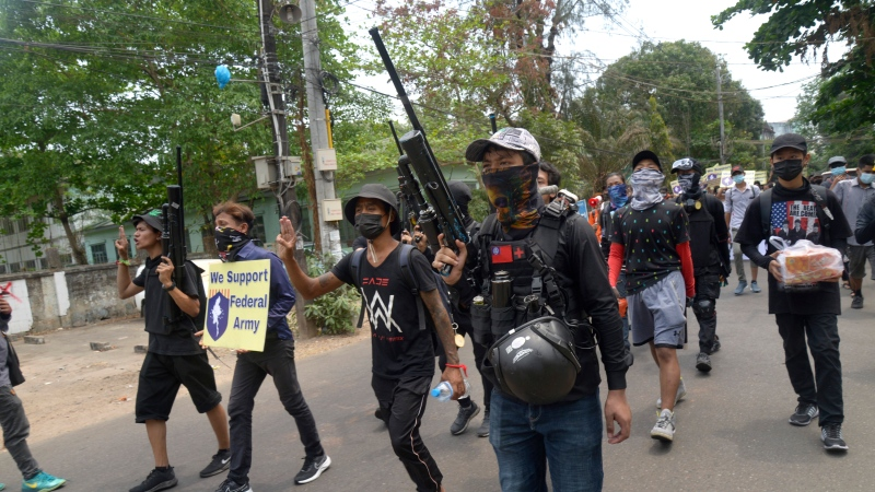 Anti-coup protesters march with homemade air rifles as one of them holds sign showing support for a civilian-formed federal army during a protest march in Yangon, Myanmar, Saturday, April 3, 2021. (AP Photo)