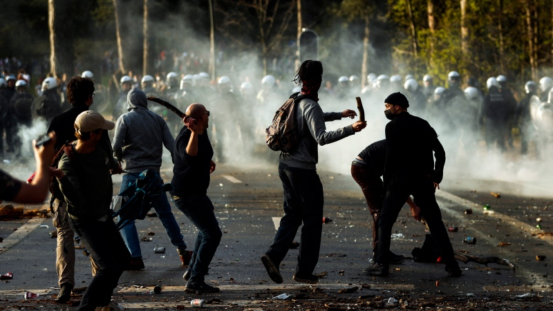 Protesters clash with police during protests in Brussels, Thursday, April 1, 2021. Belgian police have clashed with a large crowd in one of Brussels' biggest parks. Thousands of revellers had gathered for an unauthorized event despite coronavirus restrictions. (AP Photo/Fran Seco)