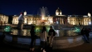 People talk as the fountain at Trafalgar is illuminated to signify a 'beacon of remembrance' in London, Tuesday, March 23, 2021, backdropped by the National Gallery of art. (AP Photo/Frank Augstein)