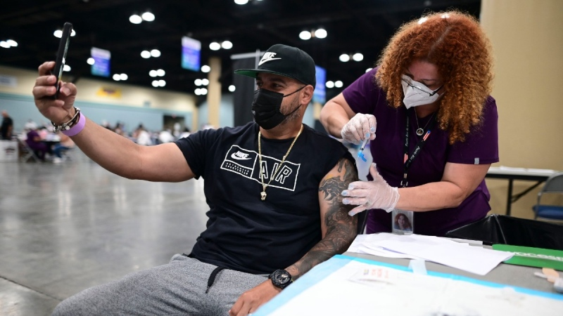 Ricardo Dieppa takes a selfie as Dr. Lourdes Marrero inoculates him with the Johnson and Johnson vaccine during a mass vaccination event carried out by the Department of Health and the Voces nonprofit organization, at the Miramar Convention Center in San Juan, Puerto Rico, on March 31, 2021. (Carlos Giusti / AP)