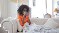 A young woman sits on the couch and blows her nose into tissues in this stock image. (Andrea Piaquadio/Pexels)