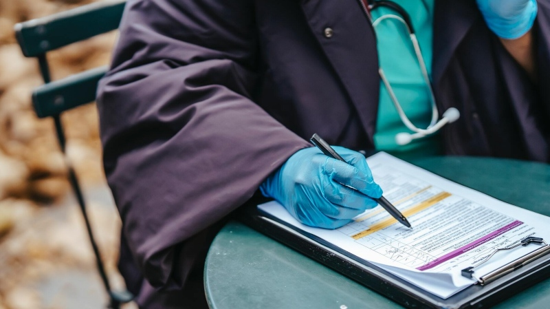 A file photo of a medical professional writing on a clipboard. (Pexels, Laura James)