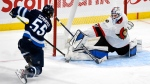 Ottawa Senators goaltender Anton Forsberg (31) makes a save on Winnipeg Jets' Mark Scheifele (55) during third period NHL action in Winnipeg on Monday, April 5, 2021. THE CANADIAN PRESS/Fred Greenslade