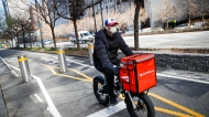 In this March 16, 2020 file photo, a delivery worker rides his bicycle along a path on the West Side Highway in New York. (AP Photo/John Minchillo, File)
