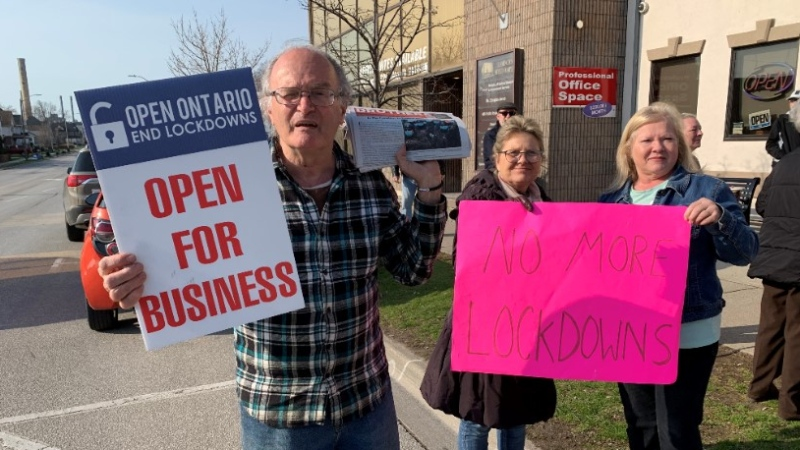 People hold signs outside a restaurant that is remaining open to in-person dining in Leamington, Ont., on Tuesday, April 6, 2021. (Bob Bellacicco / CTV Windsor)