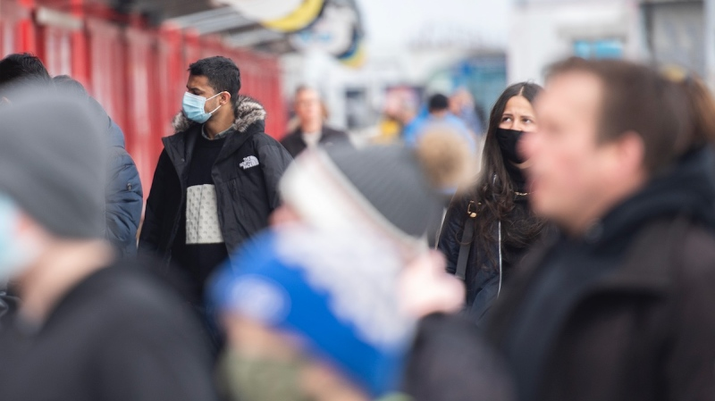 People wear face masks as they browse at an outdoor boutique in the Old Port in Montreal, Sunday, April 4, 2021. THE CANADIAN PRESS/Graham Hughes