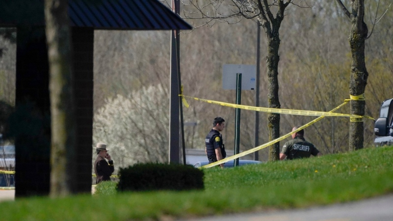 Police stand around an area cordoned off by police tape on Progress Court, near the scene of a shooting at a business park, in Frederick, Md., on April 6, 2021. (Julio Cortez / AP)