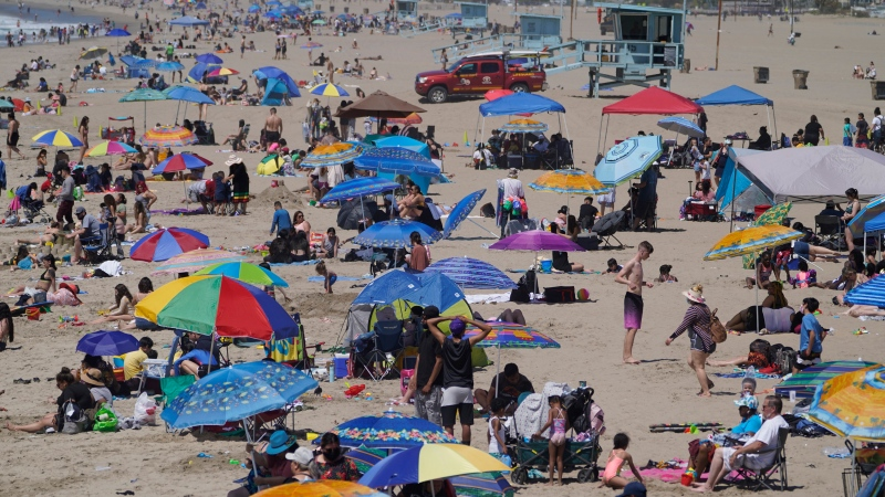People enjoy the hot weather on Santa Monica Beach in Santa Monica, Calif., Wednesday, March 31, 2021. (AP Photo/Damian Dovarganes)
