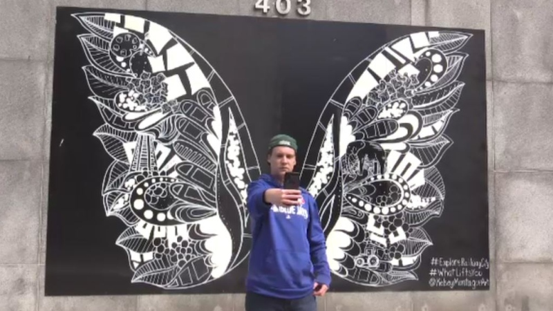 "Wesley Shaw takes a selfie with the 'Wings"" mural by artist Kelsey Montague in St. Thomas, Ont. on April 6, 2021. (Brent Lale/CTV London)"