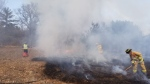 Ottawa firefighters battle an open air grass fire in this undated photo. (Image courtesy of Ottawa Fire Services)