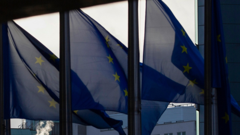 Smoke rises from a chimney behind EU flags fluttering in the wind outside EU headquarters in Brussels, Thursday, Dec. 24, 2020. (AP Photo/Virginia Mayo)