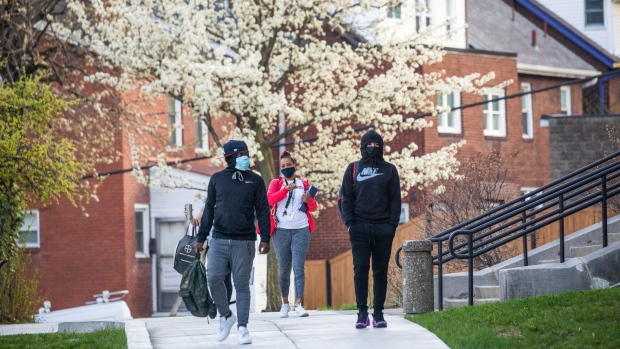Tenth grader Angelo Murphy, left, and ninth-grader Aaron Benton walk to Allderdice High School on the first day of in-person instruction for Pittsburgh Public Schools on Tuesday, April 6, 2021, in Pittsburgh. (Andrew Rush/Pittsburgh Post-Gazette via AP)