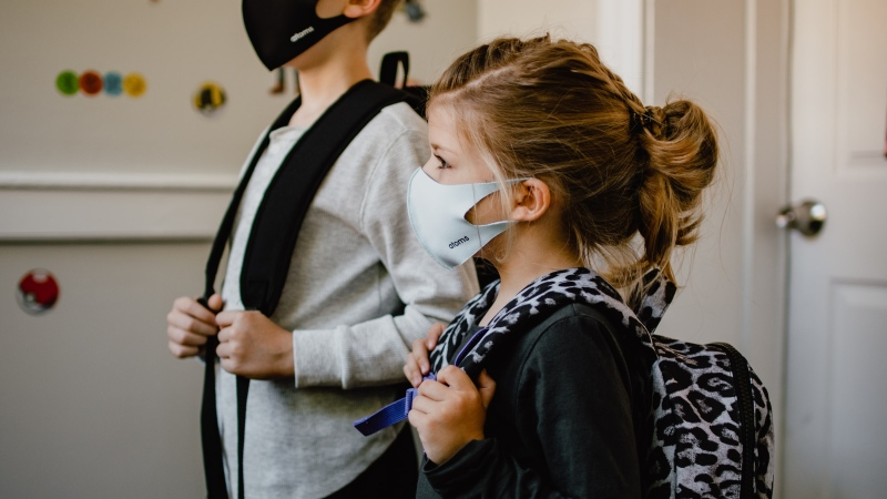 Two kids stands side-by-side wearing masks as they prepare to go to school during the COVID-19 pandemic.  (Photo by Kelly Sikkema on Unsplash)
