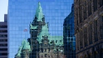 The Confederation Building reflects off the windows of a building in downtown Ottawa on Wednesday, April 7, 2020. (Sean Kilpatrick/THE CANADIAN PRESS)