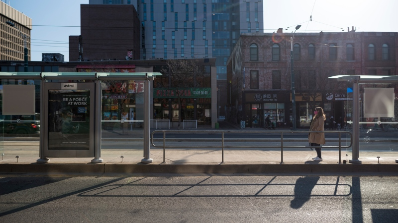 A lone commuter waits for the street car in Toronto on Wednesday, April 7, 2021. THE CANADIAN PRESS/Tijana Martin