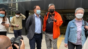 Pro-democracy activists Lee Cheuk-yan, second from right, and Yeng Sum, a former chairman of the Democratic Party, third from right, speak to media after being released on bail at a court in Hong Kong, Wednesday, April 7, 2021. (AP Photo/Rafael Wober)