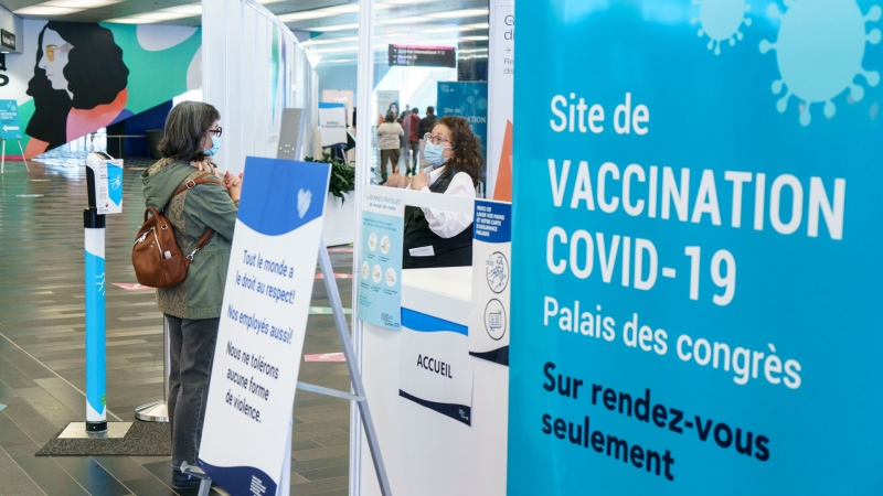 A patient is greeted at a COVID-19 vaccination clinic at the Convention Centre in Montreal, on Wednesday, April 7, 2021. THE CANADIAN PRESS/Paul Chiasson