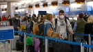 Travellers wearing protective face masks wait to check their bags at Miami International Airport on Monday, Dec. 28, 2020, in Miami. (David Santiago/Miami Herald via AP)