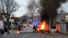 A bus burns on the Shankill road in West Belfast, Northern Ireland, Wednesday, April 7, 2021. Loyalist violence continues across many parts of Northern Ireland over the Northern Ireland Protocol. (AP Photo/Peter Morrison)