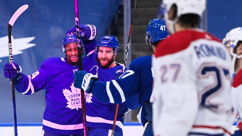 Toronto Maple Leafs defenceman TJ Brodie (78) celebrates his goal with teammate Wayne Simmonds (24) as Montreal Canadiens defenceman Alexander Romanov (27) looks on during third period NHL hockey action in Toronto on Wednesday, April 7, 2021. THE CANADIAN PRESS/Nathan Denette