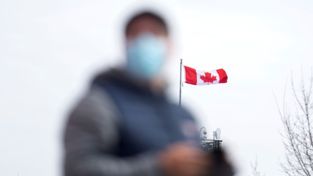 The Canadian flag flaps behind a man wearing a face mask in Montreal, Sunday, April 4, 2021. THE CANADIAN PRESS/Graham Hughes