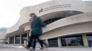 People walk past the Museum of History Saturday, March 14, 2020 in Gatineau, Que. The museum was one of many public spaces that closed its doors due to COVID-19. THE CANADIAN PRESS/Adrian Wyld