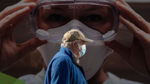 A man wears a protective face mask to help prevent the spread of COVID-19 as he walks past a billboard from the Vancouver General Hospital in Vancouver Thursday, April 8, 2021. THE CANADIAN PRESS/Jonathan Hayward